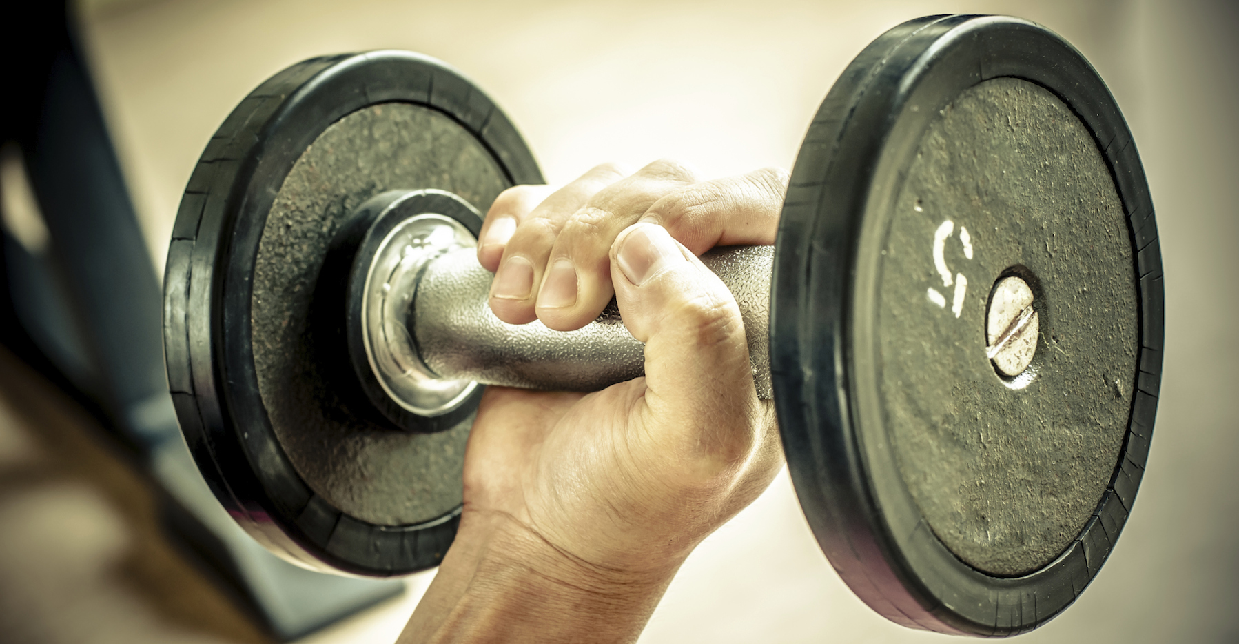 strong man's hand takes a heavy dumbbell